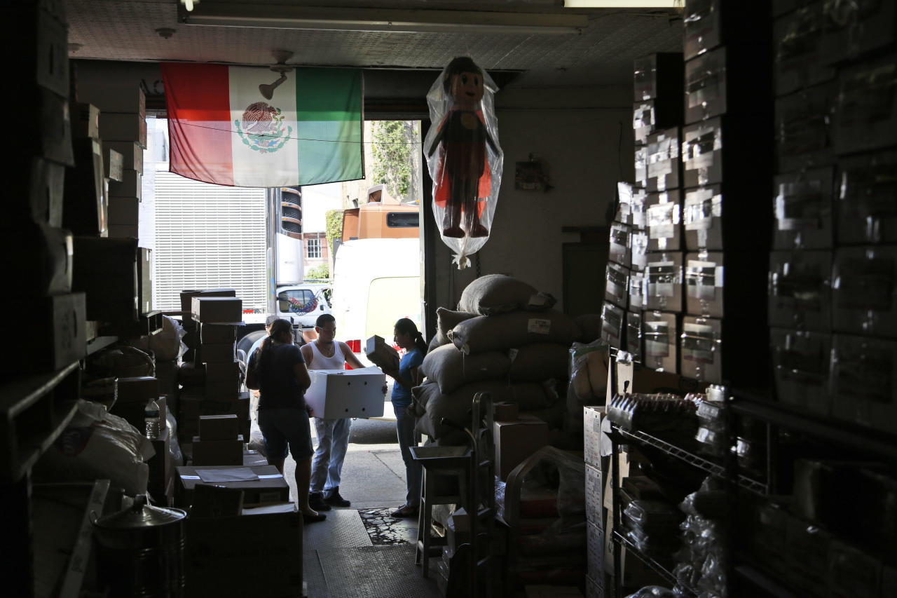 "In this Tuesday, July 18, 2017 photo, a Mexican flag hangs over the entrance to Lino Cruz's warehouse in Passaic, N.J., a city 12 miles from Manhattan, has become a second Puebla for many Mexicans who moved here from the state of Puebla in search of a better life. Mexican taquerias, bakeries and ""quinceañeras"" dress shops are spread throughout downtown, which also has a Puebla government office, a Mexican deputy mayor and some of the main distributors of Mexican food in the Northeast. (AP Photo/Seth Wenig)"