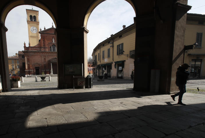In this photo taken on Thursday, March 12, 2020, a man walks in Codogno, Italy. The northern Italian town that recorded Italy's first coronavirus infection has offered a virtuous example to fellow Italians, now facing an unprecedented nationwide lockdown, that by staying home, trends can reverse. Infections of the new virus have not stopped in Codogno, which still has registered the most of any of the 10 Lombardy towns Italy's original red zone, but they have slowed. For most people, the new coronavirus causes only mild or moderate symptoms. For some it can cause more severe illness. (AP Photo/Antonio Calanni)