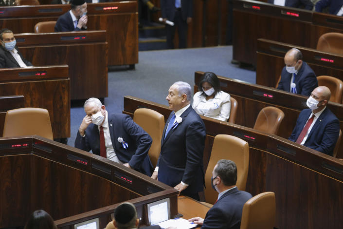 Israeli Prime Minister Benjamin Netanyahu, center, and Defense Minister Benny Gantz, center left, and other lawmakers attend the swearing-in ceremony for Israel's 24th government, at the Knesset, or parliament, in Jerusalem, Tuesday, April 6, 2021. The ceremony took place shortly after the country's president asked Netanyahu to form a new majority coalition, a difficult task given the deep divisions in the fragmented parliament. (Alex Kolomoisky/Pool via AP)