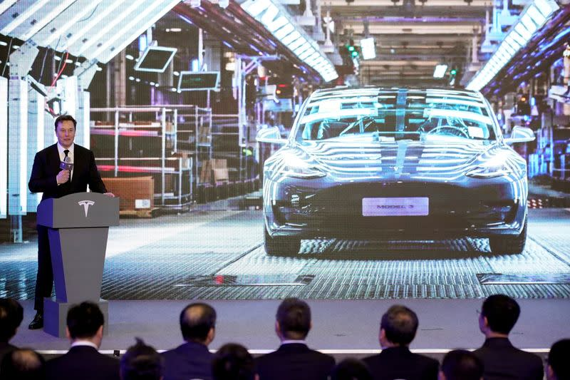 FILE PHOTO: Tesla Inc CEO Elon Musk speaks next to a screen showing an image of Tesla Model 3 car during an opening ceremony for Tesla China-made Model Y program in Shanghai