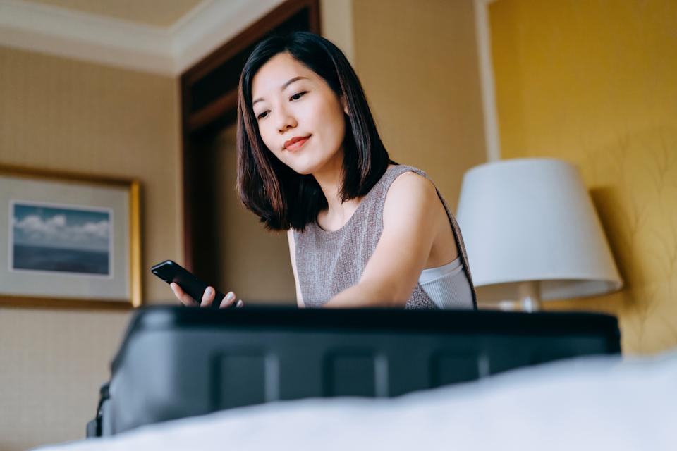 Young Asian woman using smartphone, checking the travel checklist while packing a suitcase on bed for a trip at home. Staycation, travel and vacation concept