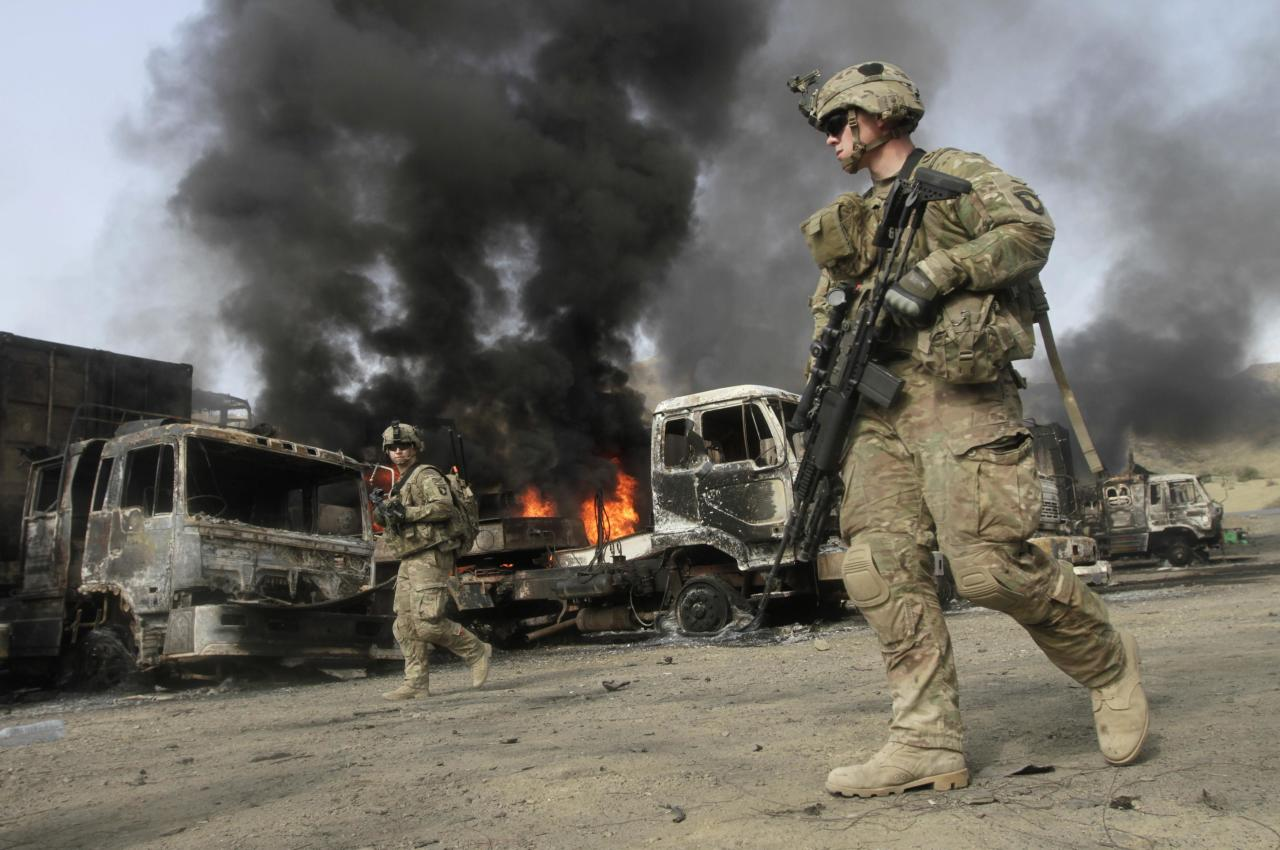 NATO troops walk near burning NATO supply trucks after, what police officials say, was an attack by militants in the Torkham area near the Pakistani-Afghan in Nangarhar Province June 19, 2014. According to officials on Thursday, at least 37 trucks belonging to NATO forces were destroyed after three suicide bombers targeted the NATO supply trucks, with two civilians wounded in the attack. REUTERS/ Parwiz (AFGHANISTAN - Tags: CIVIL UNREST POLITICS MILITARY TPX IMAGES OF THE DAY)