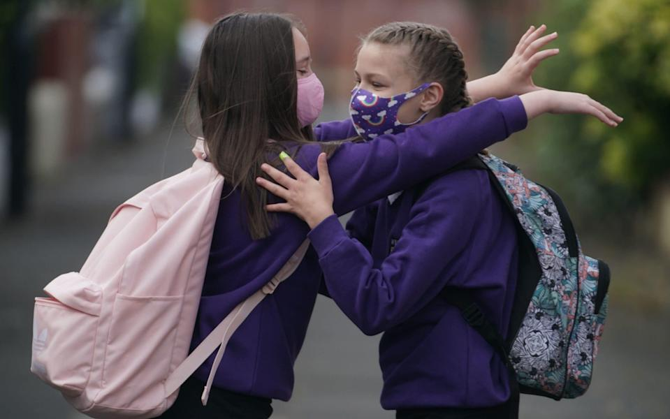 Pupils at a school in Tyne and Wear greet each other at the start of term in September. The use of face masks in schools was previously left to the discretion of headteachers - PA