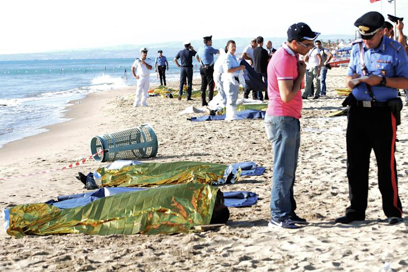 Italian police officers stand next to the lifeless bodies of six migrants who, according to Italian coast guard officials, drowned after their boat ran aground on a sandbar and they tried to swim to shore, near Catania, southern Italy, Saturday, Aug. 10, 2013. The boat, with some 100 migrants aboard, became stranded early Saturday 15 meters (50 feet) off a beach popular with tourists and locals. (AP Photo/Carmelo Imbesi)