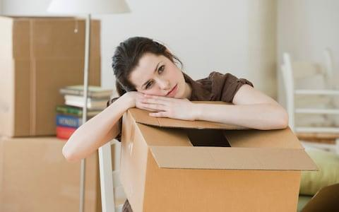 A woman resting on her moving box - Credit: Tetra images RF