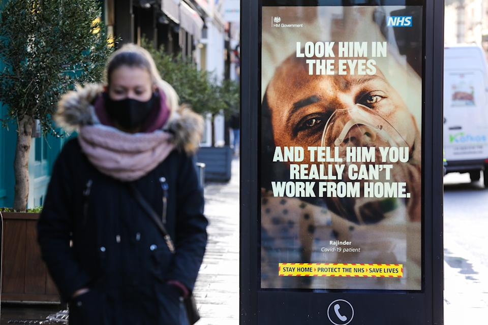 A woman wearing a face mask walks past a Covid-19 NHS publicity campaign poster in London. The UK government has said that it will vaccinate all over 50s by May 2021. (Photo by Dinendra Haria / SOPA Images/Sipa USA)