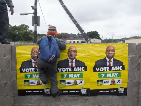 ANC election posters featuring images of South Africa's President Zuma are displayed on a wall as a school boy climbs over it in Embo