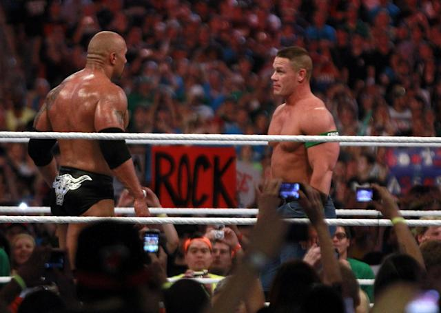 COMMERCIAL IMAGE - In this photograph taken by AP Images for WWE, Dwyane 'The Rock' Johnson, left, and John Cena face off at WrestleMania XXVIII in Sun Life Stadium on Sunday, April 1, 2012 in Miami. (Marc Serota/AP Images for WWE)