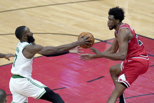 Boston Celtics' Jaylen Brown, left starts to lose control of the ball as Chicago Bulls' Thaddeus Young defends during the first half of an NBA basketball game Monday, Jan. 25, 2021, in Chicago. (AP Photo/Charles Rex Arbogast)