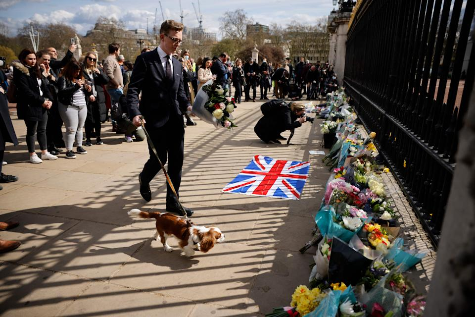 A man walking a dog approaches the floral at the railings at the front of Buckingham Palace in central London on April 9, 2021 after the annoucement of the death of Britain's Prince Philip, Duke of Edinburgh. - Queen Elizabeth II's husband Prince Philip, who recently spent more than a month in hospital and underwent a heart procedure, died on April 9, 2021, Buckingham Palace announced. He was 99. (Photo by Tolga Akmen / AFP) (Photo by TOLGA AKMEN/AFP via Getty Images)