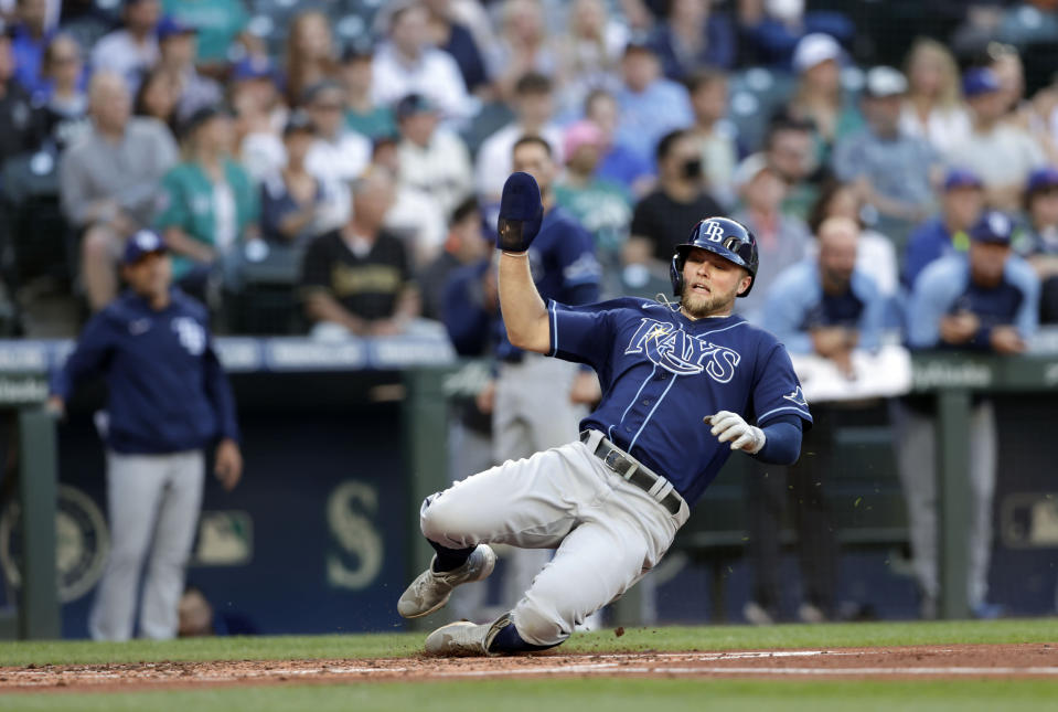 Tampa Bay Rays' Austin Meadows scores on a double by Joey Wendle during the second inning of the team's baseball game against the Seattle Mariners, Saturday, June 19, 2021, in Seattle. (AP Photo/John Froschauer)