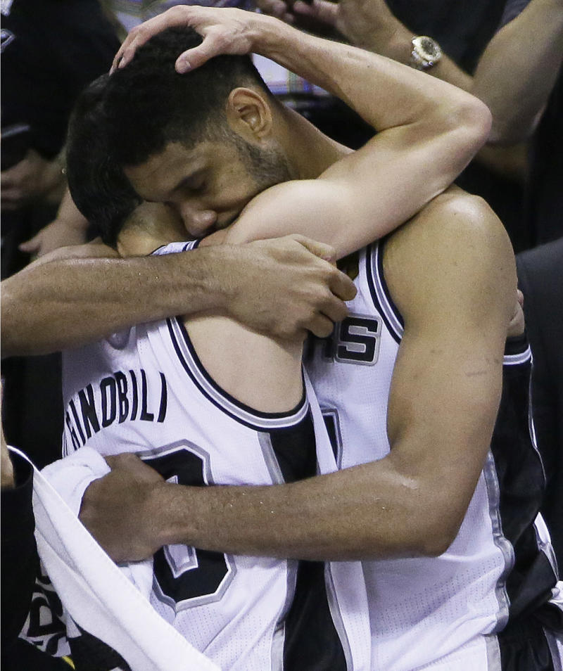 San Antonio Spurs guard Manu Ginobili, left, and forward Tim Duncan embrace in the final moments of Game 5 of the NBA basketball finals against the Miami Heat on Sunday, June 15, 2014, in San Antonio. San Antonio won the NBA championship 104-87