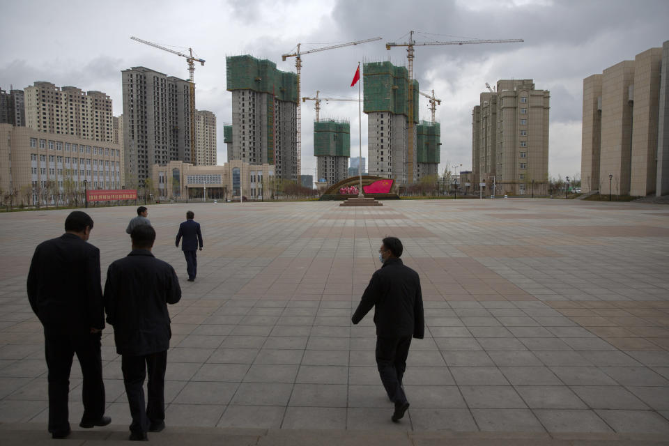 Chinese government officials walk across a plaza near a display with the Chinese flag at the Xinjiang Islamic Institute, as seen during a government organized visit for foreign journalists, in Urumqi in western China's Xinjiang Uyghur Autonomous Region on April 22, 2021. Under the weight of official policies, the future of Islam appears precarious in Xinjiang, a remote region facing Central Asia in China's northwest corner. Outside observers say scores of mosques have been demolished, which Beijing denies, and locals say the number of worshippers is on the decline. (AP Photo/Mark Schiefelbein)
