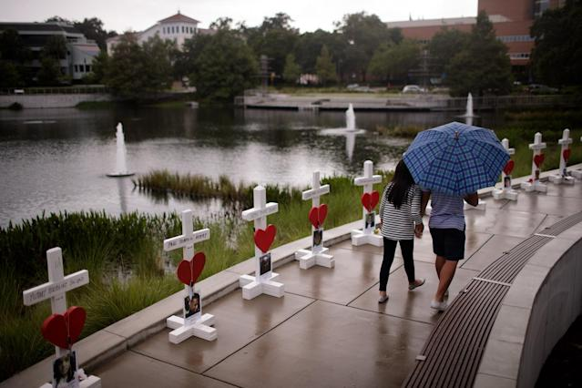 <p>A couple walks past a memorial with wooden crosses for each of the 49 victims of the Pulse Nightclub next to the Orlando Regional Medical Center, June 16, 2016 in Orlando, Florida. (Drew Angerer/Getty Images) </p>