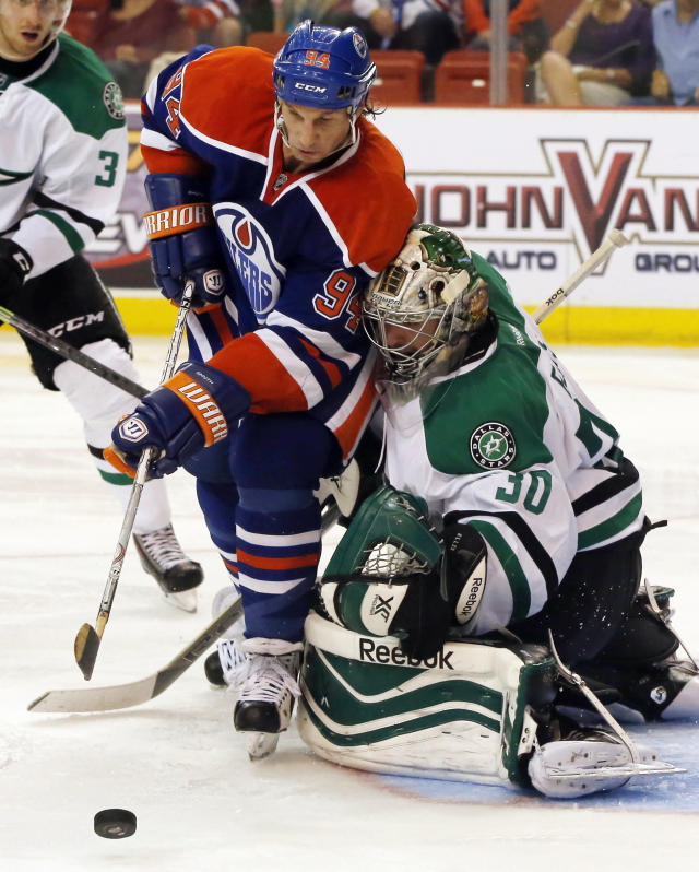 Edmonton Oilers left wing Ryan Smyth (94), of Canada, reaches past Dallas Stars goalie Dan Ellis (30), also of Canada, for the puck in the second period of an NHL preseason hockey game in Oklahoma City, Friday, Sept. 27, 2013. (AP Photo/Sue Ogrocki)