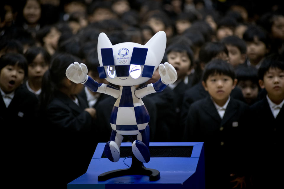 Schoolchildren pose for a picture with Tokyo 2020 Olympic Games' robot-type mascot Miraitowa during a ceremony at Hoyonomori elementary school in Tokyo on November 18, 2019. (Photo by Alessandro Di Ciommo/NurPhoto via Getty Images)
