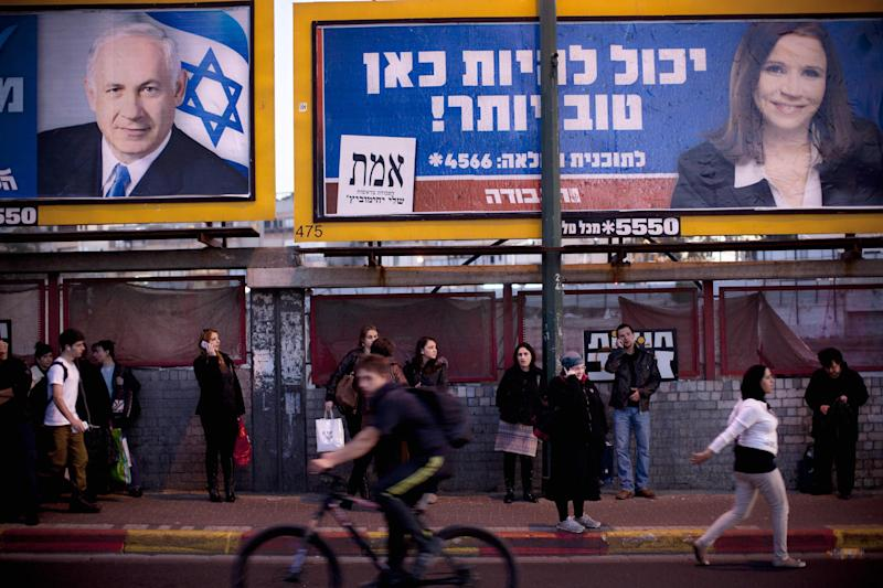 "Israelis wait for transportation under election campaign billboards of Israeli Prime Minister and Likud Party leader Benjamin Netanyahu, left, and Israel's Labor party candidate Shelly Yachimovichin, in the central Israeli city of Ramat gan, Monday, Jan. 21, 2013. The general elections will be held on Tuesday, Jan. 22, 2013. Hebrew on billboard reads, ""It can be better here."" (AP Photo/Oded Balilty)"