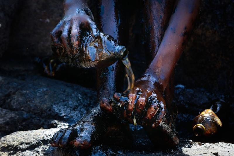 A boy cleans his foot after removing oil spilled on Itapuama beach located in the city of Cabo de Santo Agostinho, Pernambuco state, Brazil, on October 21, 2019. - Large blobs of oil staining more than 130 beaches in northeastern Brazil began appearing in early September and have now turned up along a 2,000km stretch of the Atlantic coastline. The source of the patches remain a mystery despite President Jair Bolsonaro's assertions they came from outside the country and were possibly the work of criminals. (Photo by Leo MALAFAIA / AFP) (Photo by LEO MALAFAIA/AFP via Getty Images)