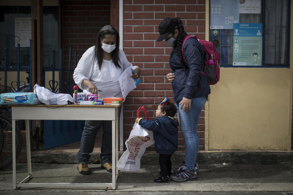 Colombian resident Alba Rada gifts toiletries and food to Venezuelan migrant Rosmira Camacho and her child, outside Rada's home where she runs her foundation, Radaber, in Tocancipa, Colombia, Tuesday, Oct. 6, 2020. For many Venezuelan migrants arriving to Colombia, the prospect of earning even less than the minimum wage is a boost, currently worth around $260 a month, far higher than Venezuela's $2. (AP Photo/Ivan Valencia)