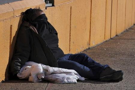 A homeless man rests on the street in New York January 4, 2016. REUTERS/Lucas Jackson