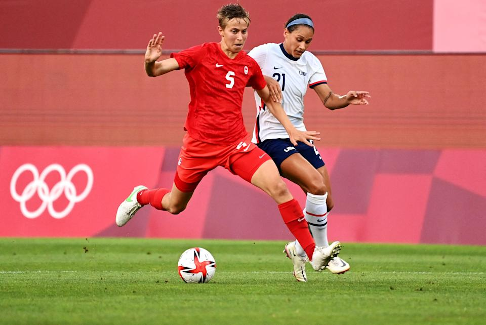 Canada's midfielder Quinn is marked by USA's forward Lynn Williams (R) during the Tokyo 2020 Olympic Games women's semi-final football match between the United States and Canada at Ibaraki Kashima Stadium in Kashima on August 2, 2021. (Photo by MARTIN BERNETTI / AFP) (Photo by MARTIN BERNETTI/AFP via Getty Images)
