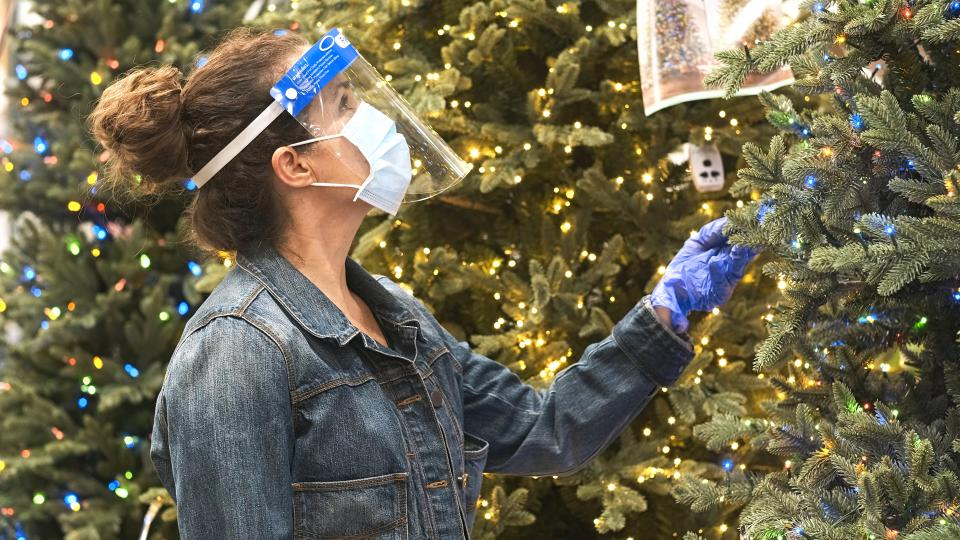 Mature caucasian woman shopping for Artificial Christmas Tree inside a megastore wearing a protective face mask, a face shield and protective gloves