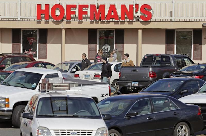 Cars jam the parking lot as shoppers leave Hoffman's Gun Center with their purchases in Newington, Conn., Tuesday, April 2, 2013. Customers are packing gun stores around Connecticut following the unveiling of new gun-control legislation, which could take effect as soon as Wednesday evening. (AP Photo/Charles Krupa)