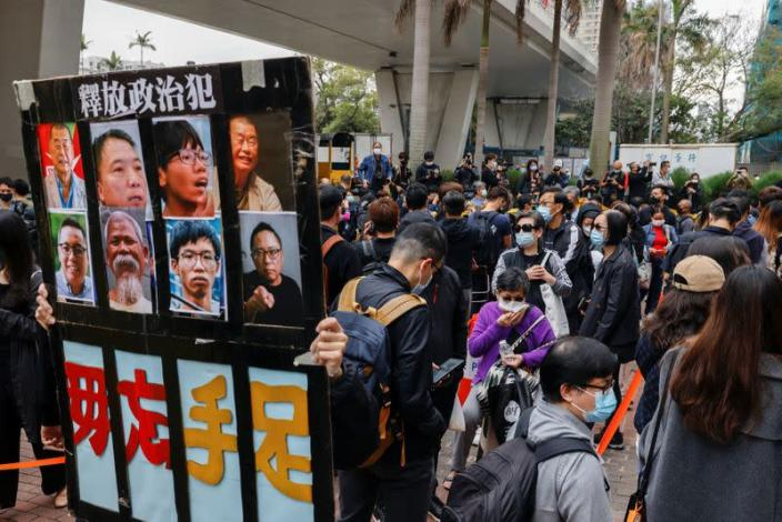 A supporter holds a sign with photos of pro-democracy activists while queuing up for the court hearing over national security law outside West Kowloon Magistrates' Courts, in Hong Kong