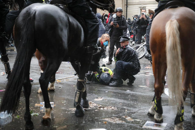 A colleague attends to a police officer who was injured when falling off a horse during a Black Lives Matter rally at Downing Street on Saturday (AP Photo)