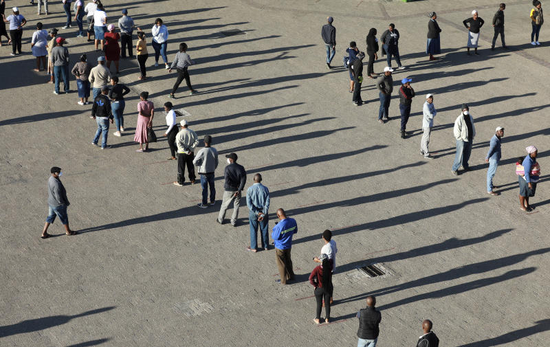 In this photo taken Thursday, April 2, 2020 people practice social distancing outside a testing clinic in Khayelitsha, Cape Town, South Africa. South Africa, one of the world's most unequal countries with a large population vulnerable to the new coronavirus, may have an advantage in the coronavirus outbreak, honed during years battling HIV and tuberculosis: the know-how and infrastructure to conduct mass testing. (AP Photo/Nardus Engelbrecht)