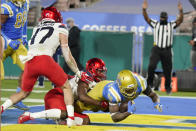 UCLA running back Brittain Brown, right, lunges into the end zone for a touchdown after a reception during the first half of an NCAA college football game against the Arizona onSaturday, Nov. 28, 2020, in Pasadena, Calif. (AP Photo/Marcio Jose Sanchez)
