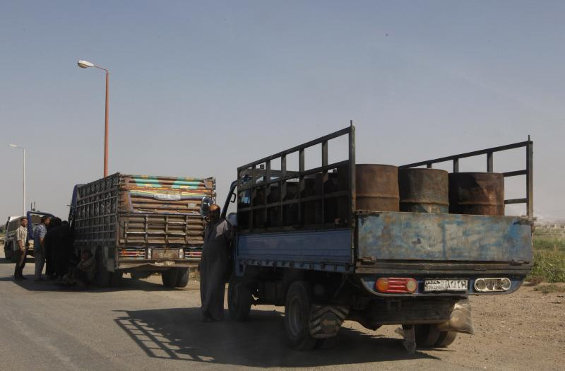 Diesel and gasoline barrels are seen on trucks along a highway in Raqqa