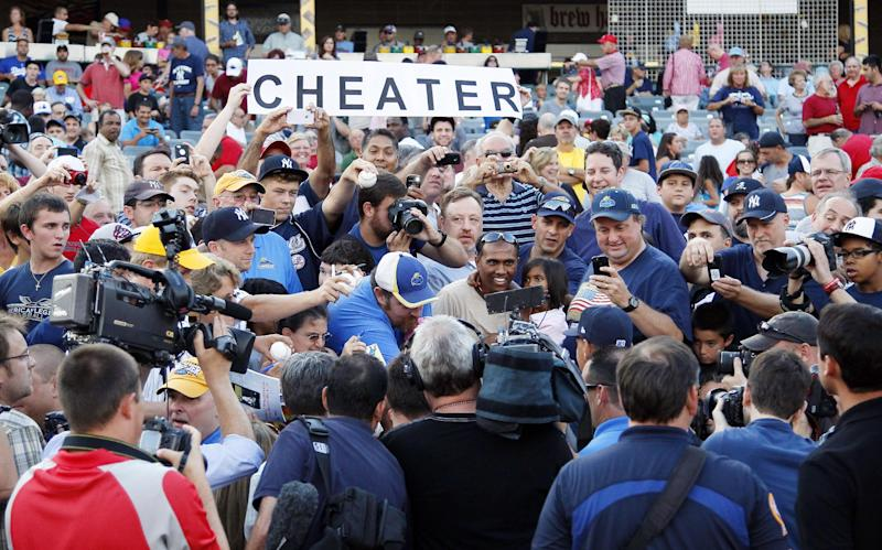 """A fan holds a sign that reads """"CHEATER,"""" as New York Yankees' Alex Rodriguez is surrounded by members of the media while singing autographs before the start of a Class AA baseball game with the Trenton Thunder against the Reading Phillies, Friday, Aug. 2, 2013, in Trenton, N.J. (AP Photo/Tom Mihalek)"""
