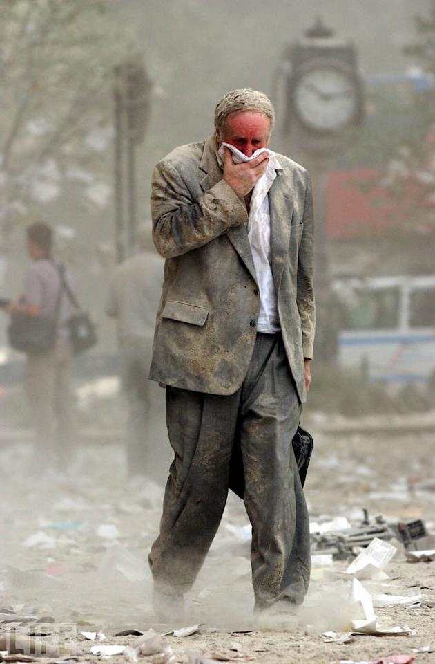 """This image (another by Stan Honda) is an exemplar of a strange, wrenching sight witnessed by innumerable people in New York on the morning of September 11: A survivor, layered in eerie, white dust, trudging away from the cataclysm. The man, Edward Fine, was an owner of an investment and public relations firm; he was on the 78th floor of 1 World Trade Center when it was hit. (Photo: STAN HONDA/AFP/Getty Images)<br><br>For the full photo collection, go to <a target=""""_blank"""" href=""""http://www.life.com/gallery/63651/confronting-terror-faces-of-911#index/0"""">LIFE.com</a><br>"""