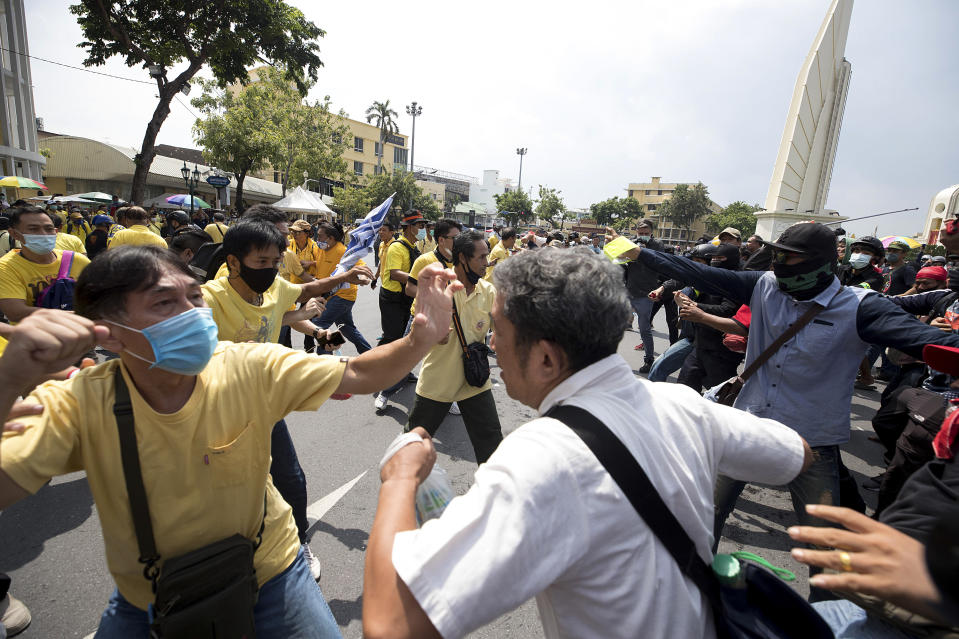A pro-democracy protester, right, and and a supporter of the monarchy, in yellow, exchange blows at a rally near the Democracy Monument in Bangkok, Thailand, Wednesday, Oct. 14, 2020. Thousands of anti-government protesters gathered Wednesday for a rally at Bangkok's Democracy Monument being held on the anniversary of a 1973 popular uprising that led to the ousting of a military dictatorship, amid a heavy police presence and fear of clashes with political opponents.(AP Photo/Wason Wanichakorn)
