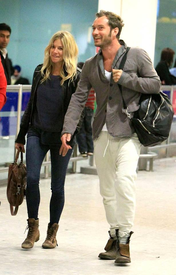 """Looking happy and relaxed, Jude Law and Sienna Miller arrived at Heathrow Airport Monday fresh from their Christmas vacation in Africa. Though Sienna was her usual chic self in skin-tight denim and a biker jacket, we're not sure what Jude was thinking with that sweat pants and blazer combo! <a href=""""http://www.pacificcoastnews.com/"""" target=""""new"""">PacificCoastNews.com</a> - January 3, 2011"""