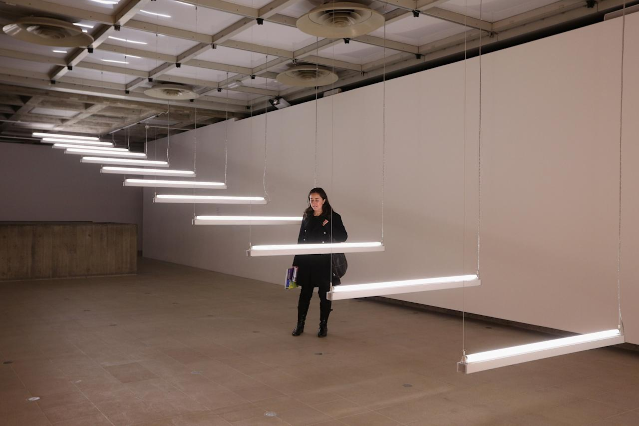 LONDON, ENGLAND - JANUARY 29:  A woman admires an art installation by Brigitte Kowanz entitled 'Light Steps' which features in the Hayward Gallery's exhibition 'Light Show' on January 29, 2013 in London, England. 'Light Show' features 25 illuminated installations and sculptures by major international artists from the 1960s to the present day. The show opens to the general public on January 30, 2013 and runs until April 28, 2013.  (Photo by Oli Scarff/Getty Images)