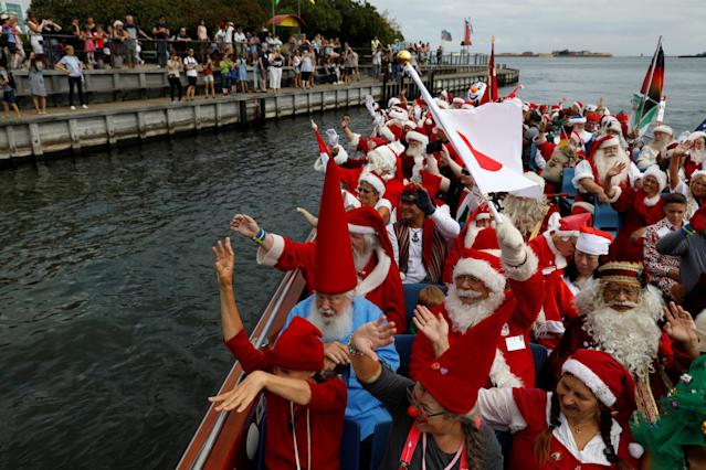 <p>People dressed as Santa Claus wave from a canal boat, as they take part in the World Santa Claus Congress, an annual event held every summer in Copenhagen, Denmark, July 23, 2018. (Photo: Andrew Kelly/Reuters) </p>