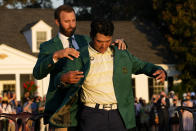 Dustin Johnson helps Hideki Matsuyama, of Japan, put on the champion's green jacket after winning the Masters golf tournament on Sunday, April 11, 2021, in Augusta, Ga. (AP Photo/David J. Phillip)