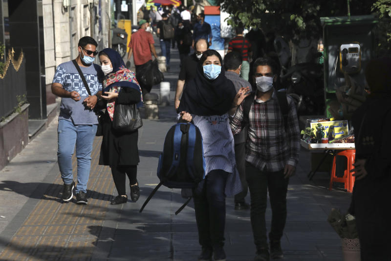 People wearing protective face masks to help prevent the spread of the coronavirus walk on a sidewalk in downtown Tehran, Iran, Sunday, Sept. 20, 2020. Iran's president dismissed U.S. efforts to restore all U.N. sanctions on the country as mounting economic pressure from Washington pushed the local currency down to its lowest level ever on Sunday. (AP Photo/Vahid Salemi)
