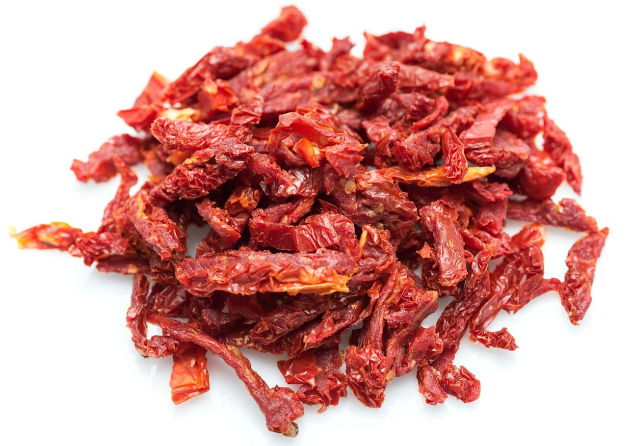 Heap of sliced sun dried tomatoes on white background