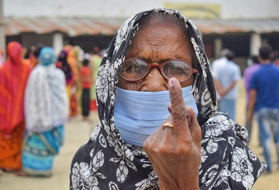 An elderly woman being brought at a polling booth to cast her vote for the 6th phase of West Bengal Assembly polls, in Nadia.