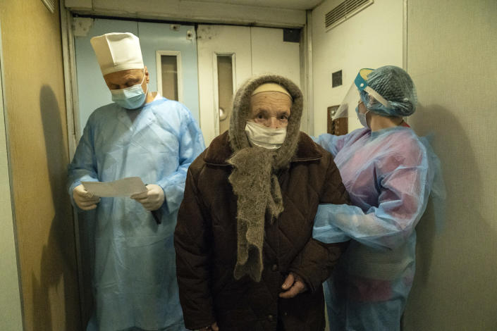 Two medical workers escort an elderly woman suffering from COVID-19 into a hospital in Kolomyia, western Ukraine, Tuesday, Feb. 23, 2021. After several delays, Ukraine finally received 500,000 doses of the AstraZeneca vaccine marketed under the name CoviShield, the first shipment of Covid-19 vaccine doses. The country of 40 million is one of the last in the region to begin inoculating its population. (AP Photo/Evgeniy Maloletka)