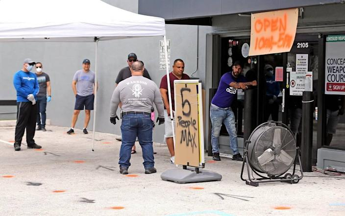 Customers line up six feet apart outside Warrior Gun Range and Gun Shop in Doral on Tuesday. Owner Charlie Berrane has seen soaring sales of guns and ammo as customers seek self-protection during the coronavirus pandemic. Stores are running out of inventory.