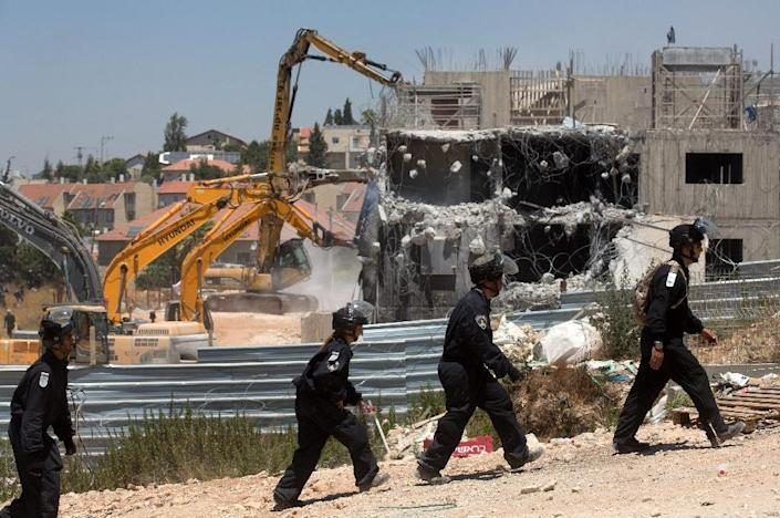 Israeli security forces stand guard as bulldozers, under an Israeli High Court ruling, start the demolition of buildings in the settlement of Beit El on July 29, 2015 (AFP Photo/Menahem Kahana)