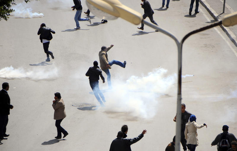 Tunisian demonstrators run for cover as police fire tear gas to break up a protest in Tunis, Monday, April 9, 2012. Tunisian policemen clashed with thousands of anti-government protesters who tried to storm Habib Bourguiba Avenue in Tunis on Monday, defying a ban on demonstrations in the area of the revolt that ousted President Zine al-Abidine Ben Ali over a year ago.  (AP Photo/Hassene Dridi)
