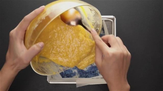 Pouring durian custard over white and blue rice layer