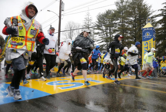 Boston Marathon bombing hero Carlos Arredondo, left, joins others as they break from the start in the mobility impaired runner division of the 122nd running of the Boston Marathon in Hopkinton, Mass., Monday, April 16, 2018. (AP Photo/Mary Schwalm)