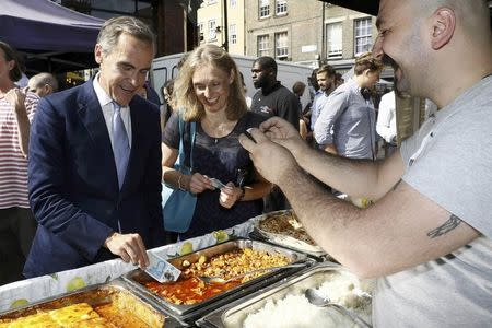 Bank of England governor Mark Carney tests a new polymer five pound note as he buys lunch at Whitecross Street Market in London, Britain September 13, 2016. REUTERS/Stefan Wermuth/File Photo