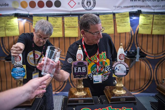<p>Bar staff serve visitors at the CAMRA (Campaign for Real Ale) Great British Beer festival at Olympia exhibition center on August 8, 2017 in London, England. (Photo: Carl Court/Getty Images) </p>